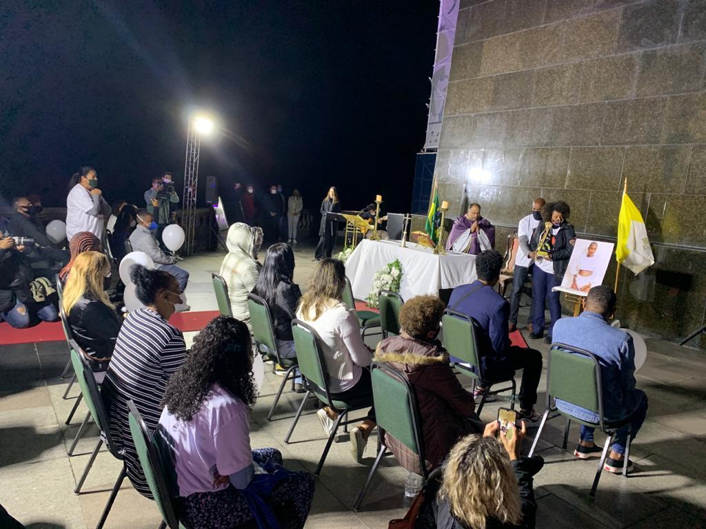 pessoas sentadas assistindo a missa