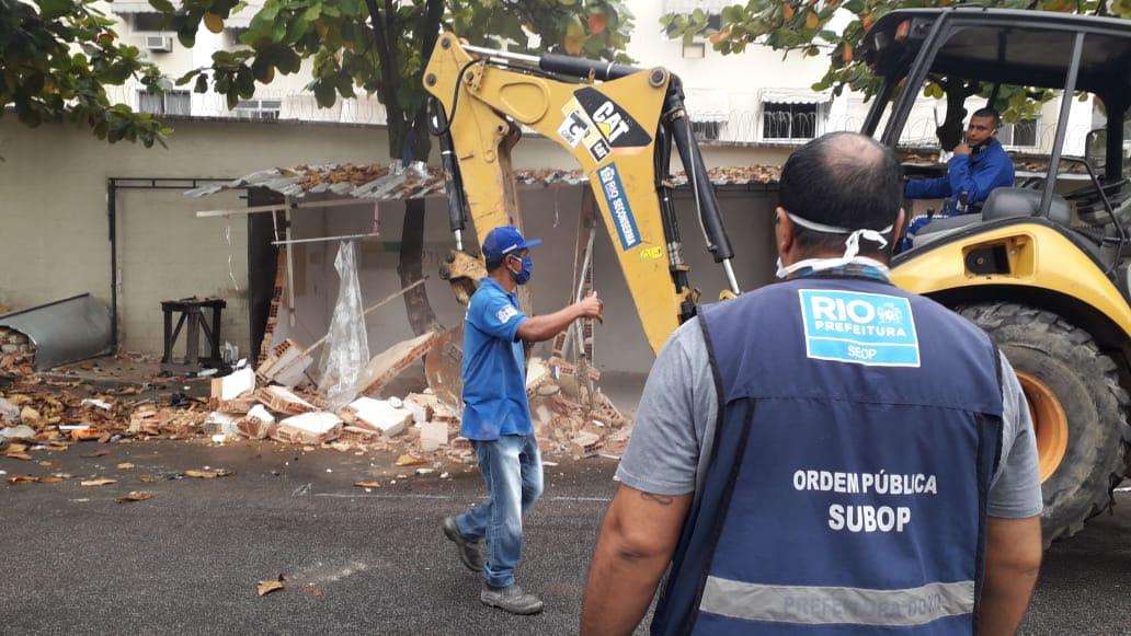 Imagem de uma retroescavadeira demolindo uma construção irregular