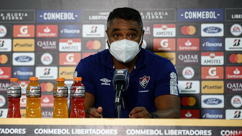 Foto: Roger Machado de máscara sentado participando de coletiva