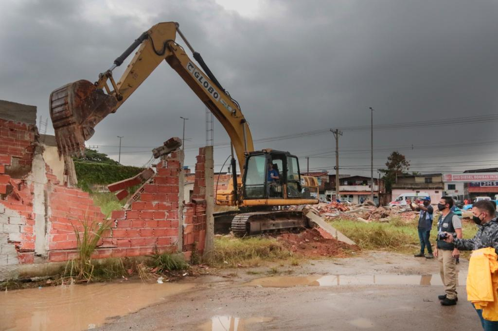 Imagem de uma retroescavadeira derrubando uma construção irregular