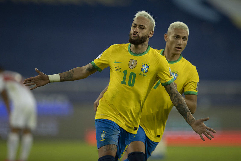 Com a camisa amarela da seleção, Neymar e Richarlison comemoram o gol do Brasil