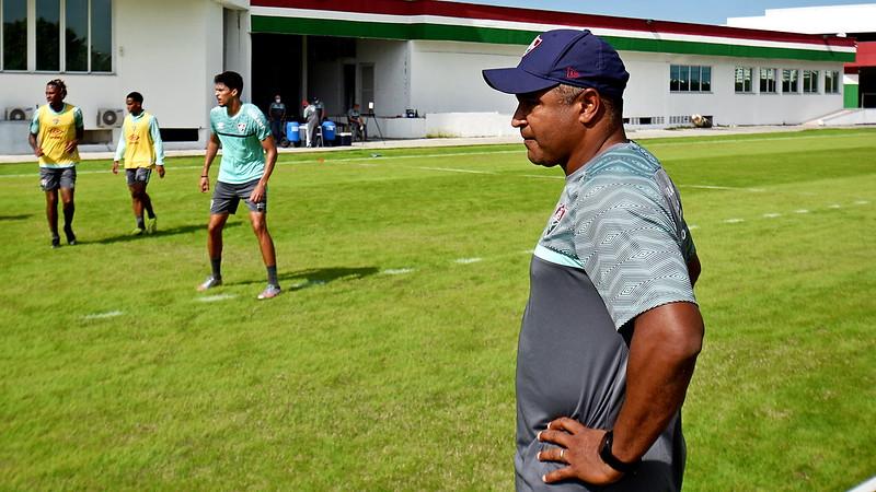 De boné roxo e camisa cinza, Roger Machado observa o treino do Fluminense