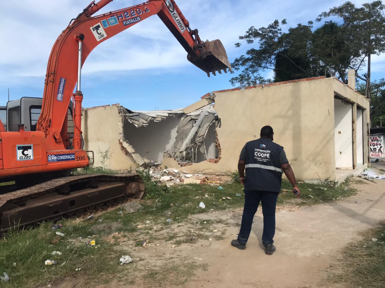 Imagem de uma retroescavadeira demolindo um casa