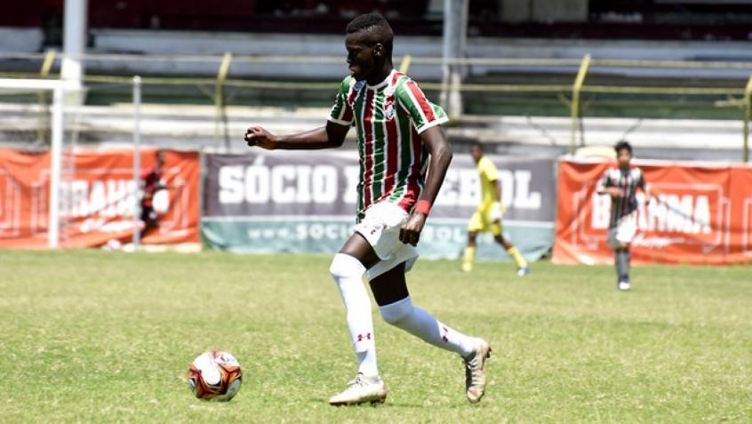 Metinho conduzindo a bola em campo pelo Fluminense