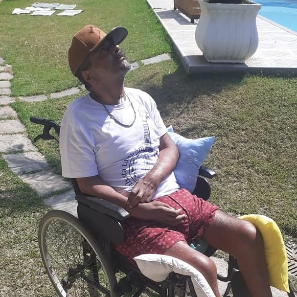 Arlindo Cruz sentado na cadeira de rodas pegando sol