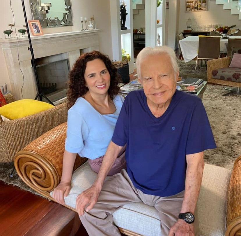 Cid Moreira e a esposa Fátima sentados no sofá na sala da casa deles
