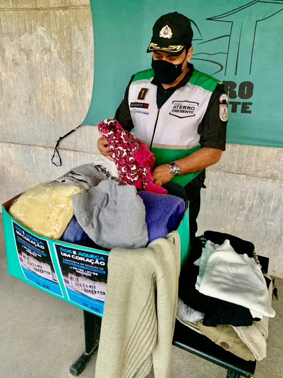 Imagem de um policial separando roupas para doações