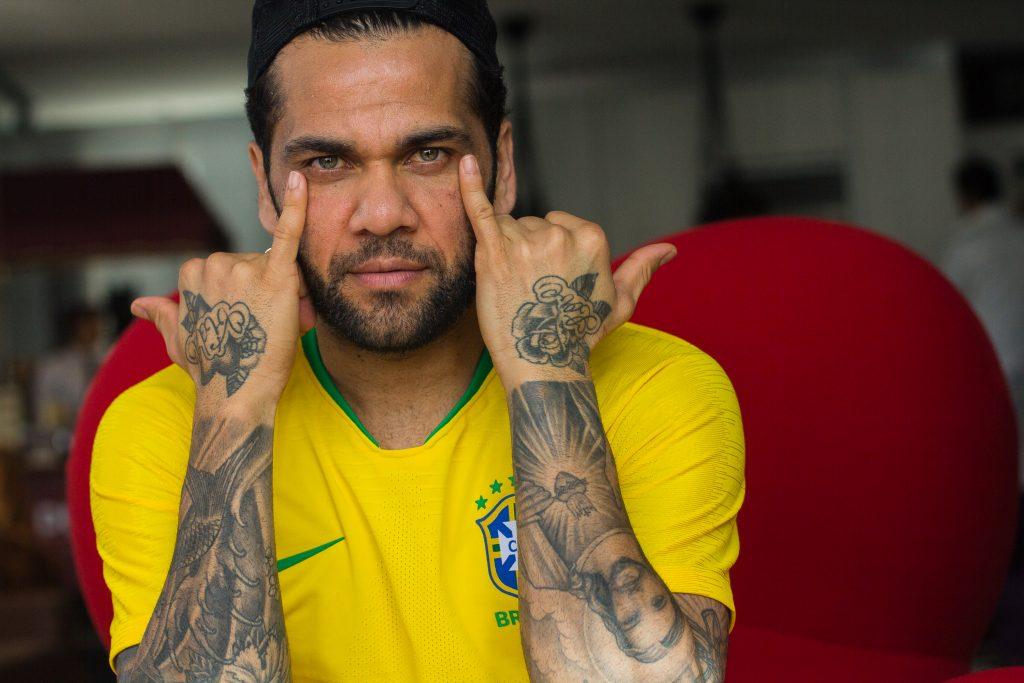 Daniel Alves com a camisa da seleção brasileira mostra tatuagens nos 2 braços e atingindo os olhos