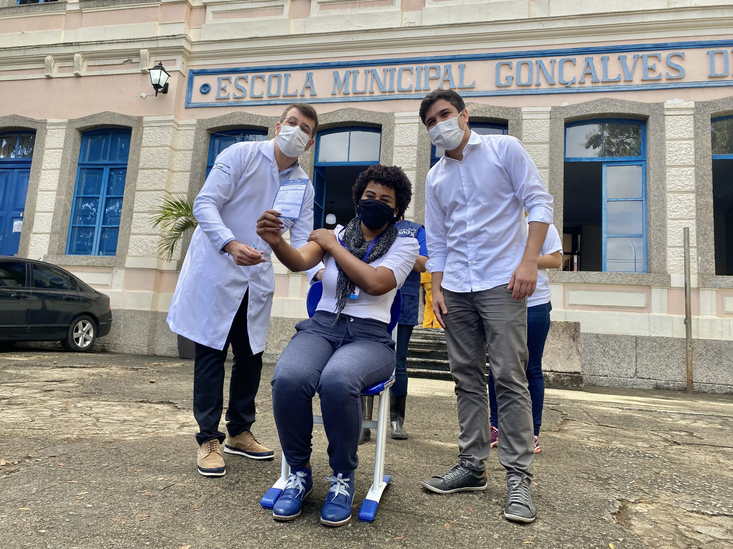 Secretários de Saúde e Educação com professora da rede municipal sendo vacinada