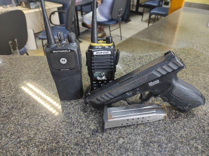 rádio de comunicação e arma em cima da mesa