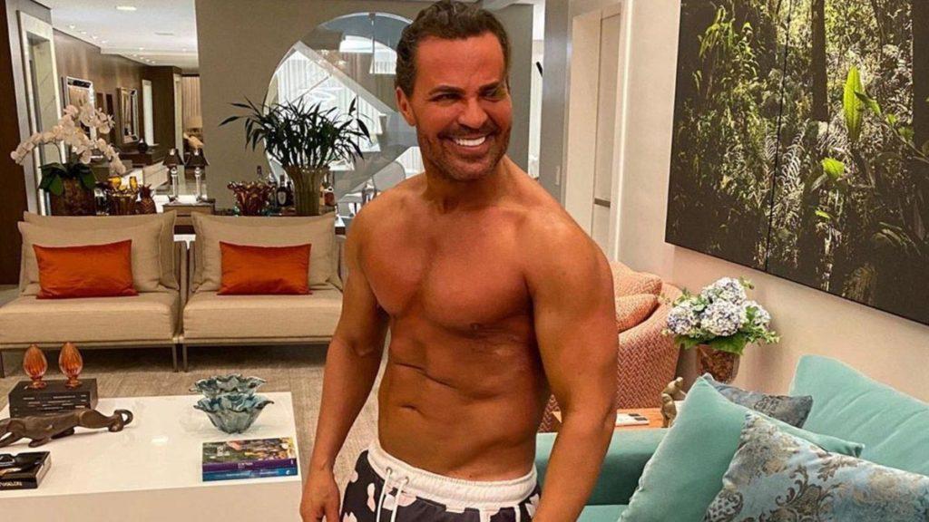 Eduardo Costa sem camisa na sala da casa dele