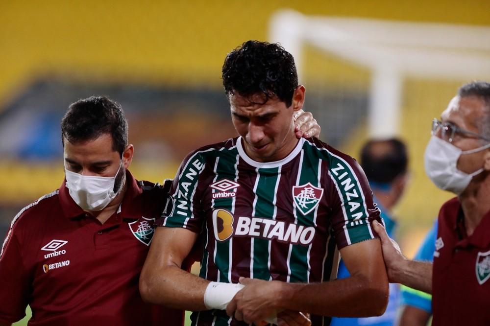 Ganso saindo de campo segurando o braço amparado por  funcionários do Fluminense