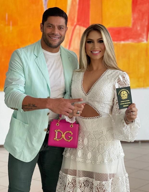 Jogador Hulk e a mulher Camila Ângelo segurando bolsa e comemorando formatura