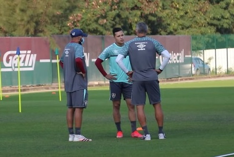 O lateral Marlon está entre dois integrantes da comissão técnica do Fluminense  no campo de treinamento