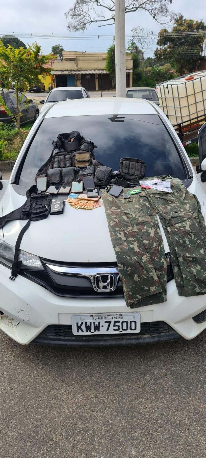 Carro roubado pelos suspeitos com cintos de guarnição, capa de colete à prova de balas e roupas camufladas