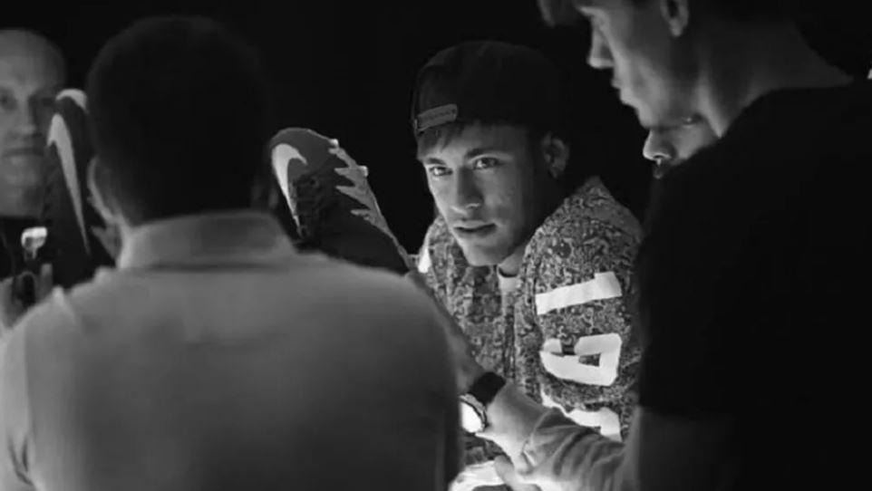 Neymar segurando uma chuteira da Nike