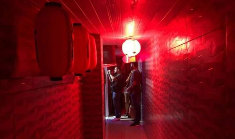 Corredor com luz vermelha e policiais civis
