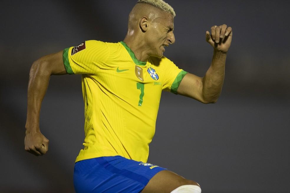 Richarlison comemorando gol com a camisa da seleção brasileira com braço esquerdo em punho no ar