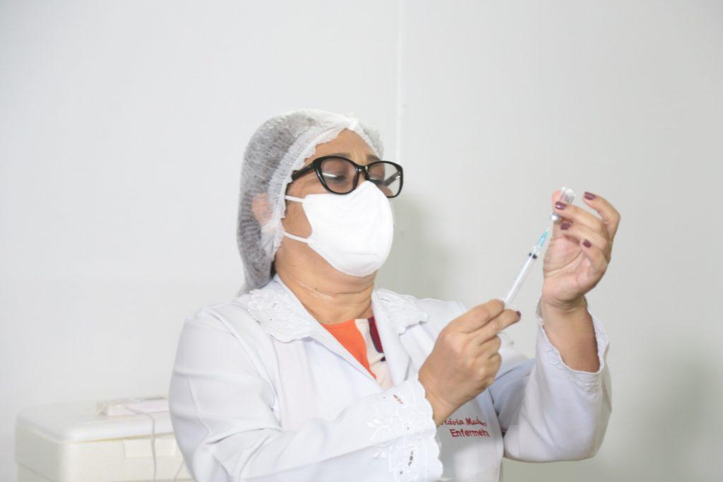 Mulher segurando uma seringa