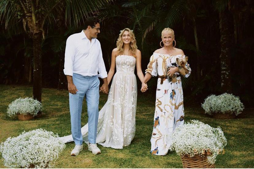 Sasha de mãos dadas com os pais Luciano Szafir e Xuxa no dia do casamento dela