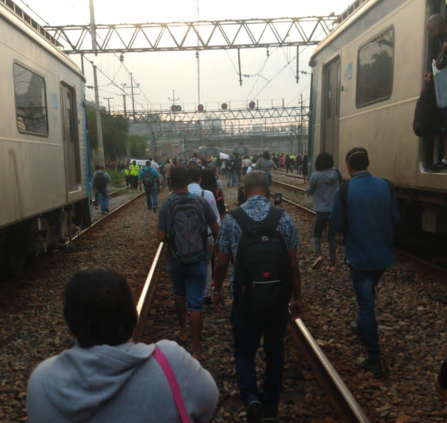 Passageiros caminhando nos trilhos.