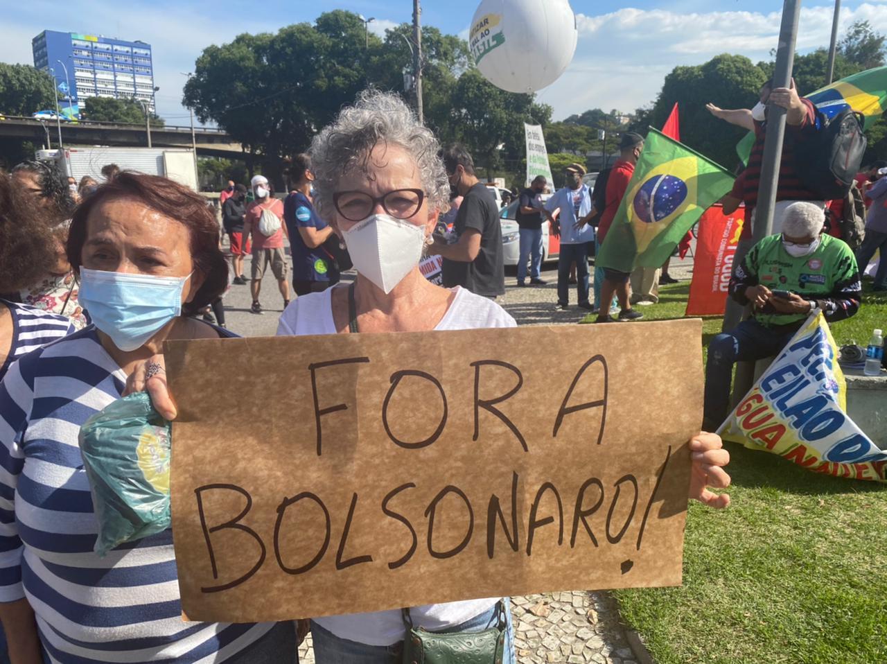 """Manifestante com um cartaz escrito """"Fora Bolsonaro"""""""