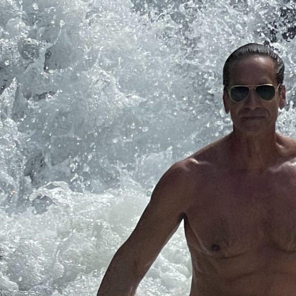 Victor Fasano sem camisa numa cachoeira