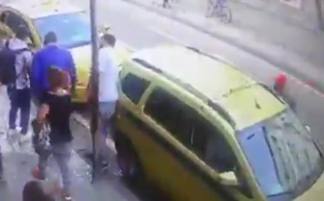 Pessoas envolta de um táxi