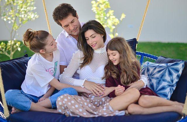 Daniel com a esposa e as filhos no sofá anunciando terceira gravidez