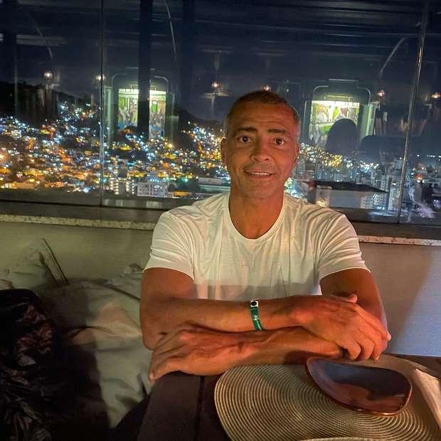 Romário sentado na mesa de um restaurante