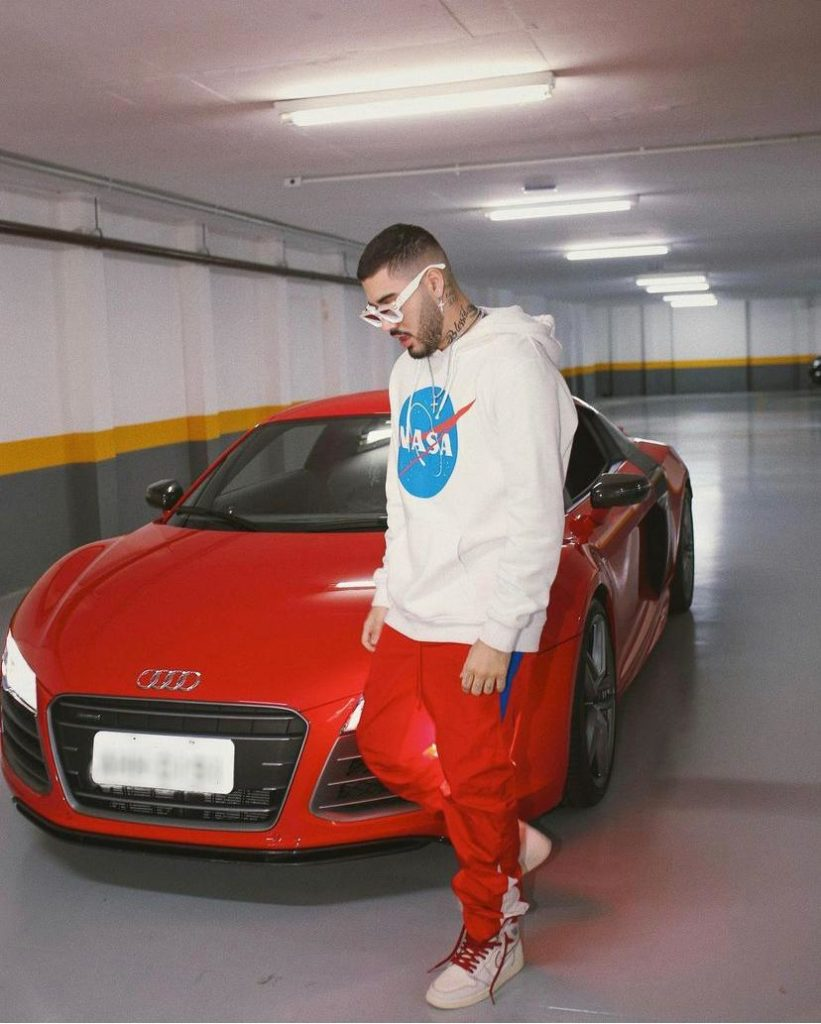 Kevinho com carro da coleção de importados que tem na garagem