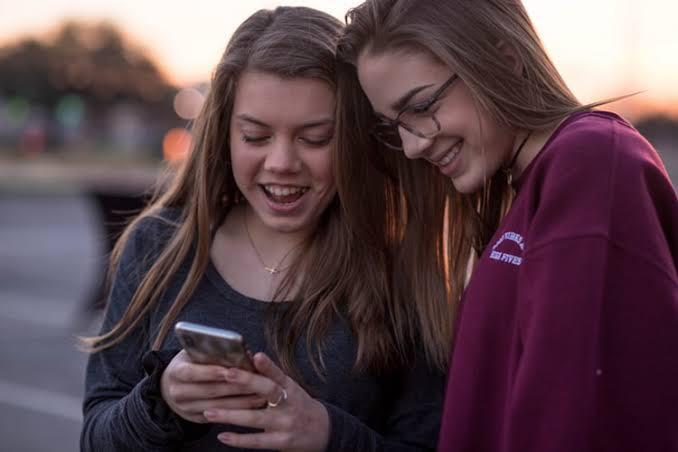 Imagem de duas jovens analisando o termo 'cringe'