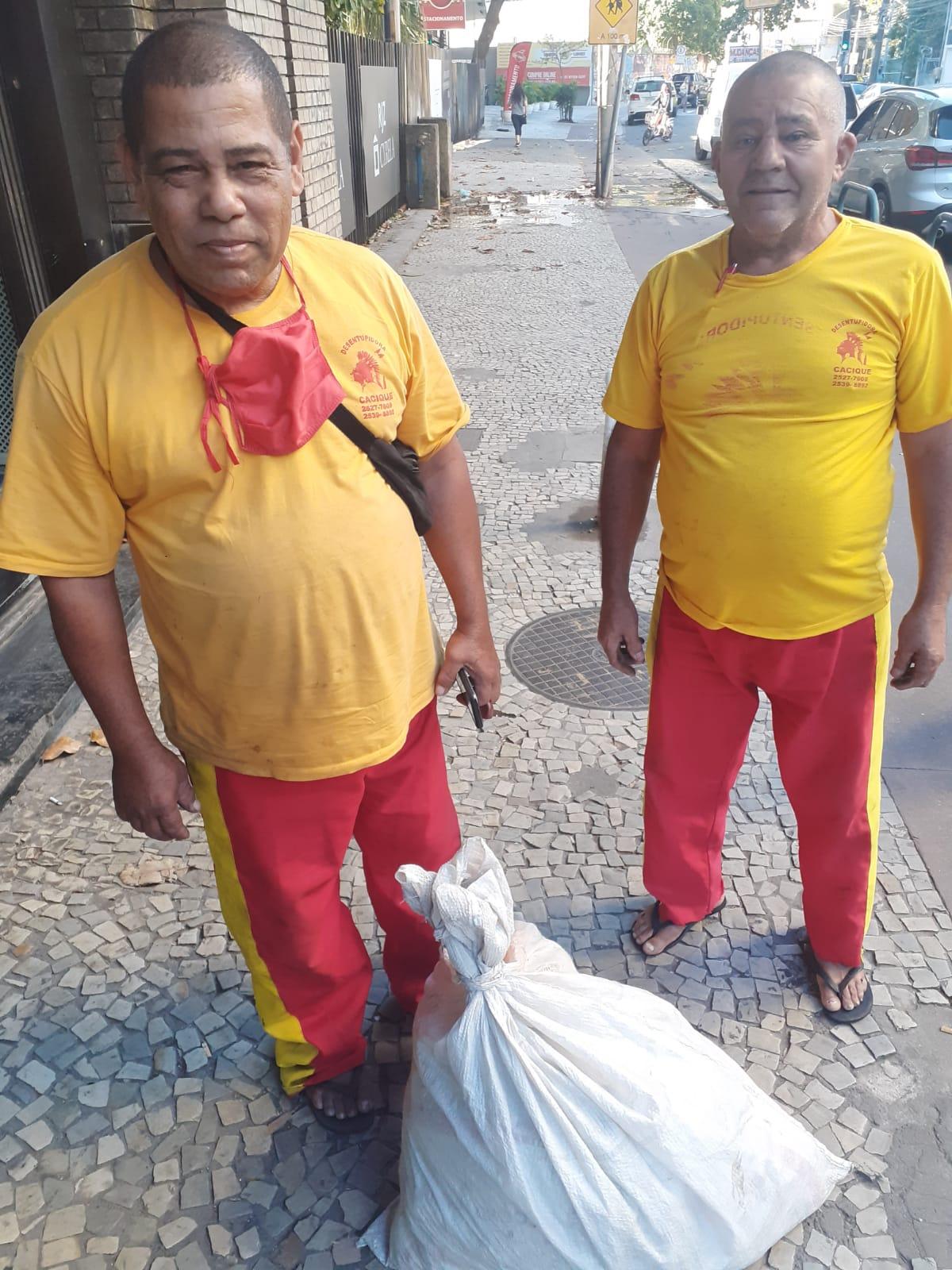 Na imagem, dois homens que encontraram uma sacola com roupas e devolveram para o dono