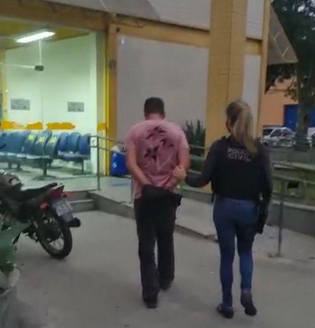 Um dos presos da operação chegando na delegacia