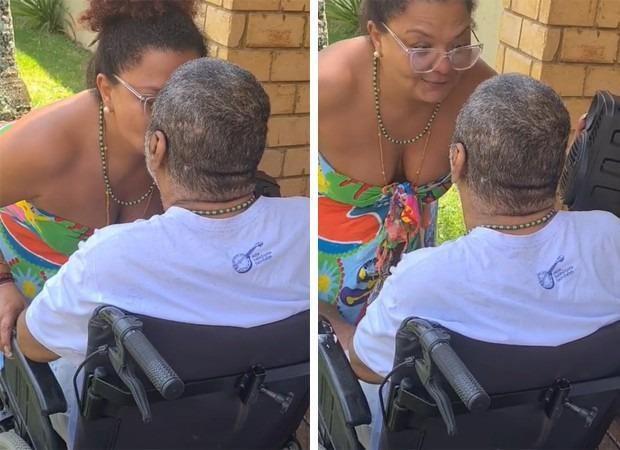 Arlindo Cruz sentado na cadeira de rodas com a esposa Babi Cruz
