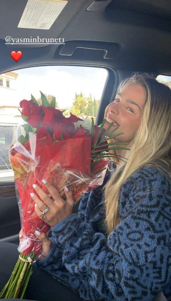 Modelo Yasmin Brunet segurando buquê de flores dentro do carro