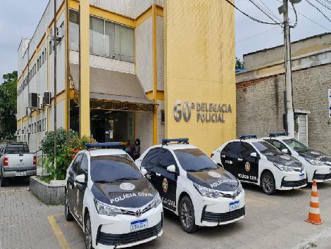 Imagem da fachada da delegacia com viaturas da Polícia Civil estacionadass