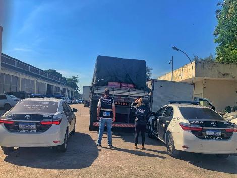 Imagem de um caminhão, duas viaturas e dois policiais