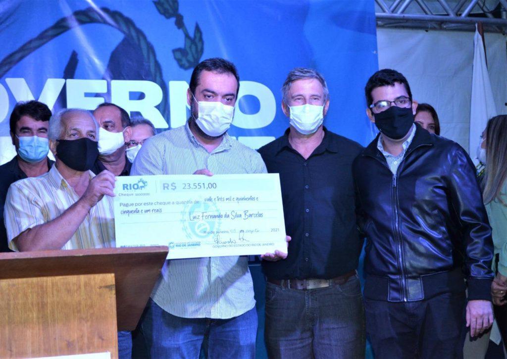 Imagem do Governador Cláudio Castro e do Secretário Marcelo Queiroz entregando cheques simbólicos  em Quissamã