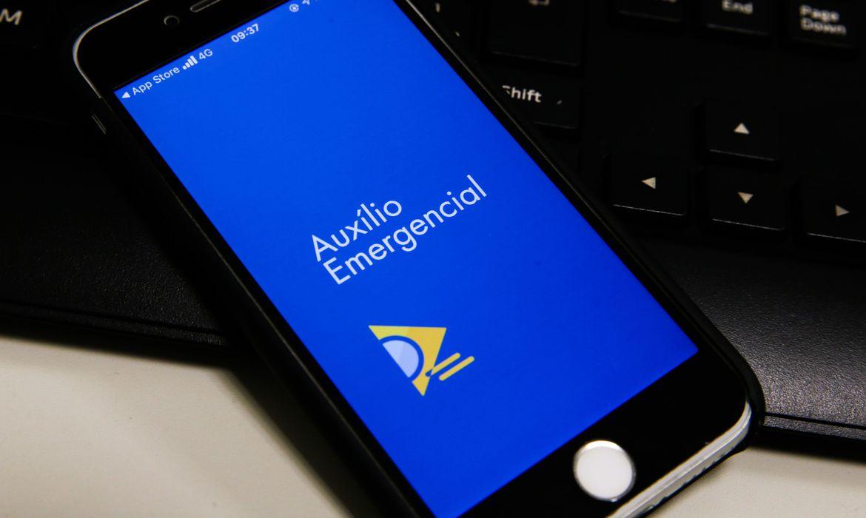 Aparelho celular com a imagem do Auxílio Emergencial
