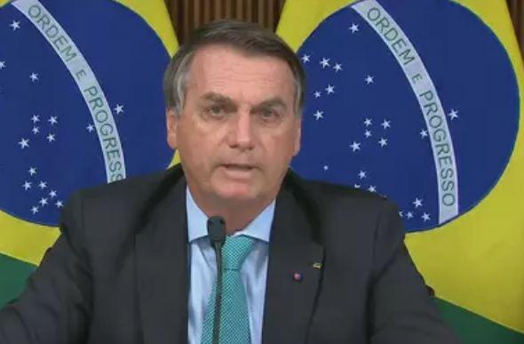 Presidente Jair Bolsonaro em foto oficial com a bandeira do Brasil de fundo