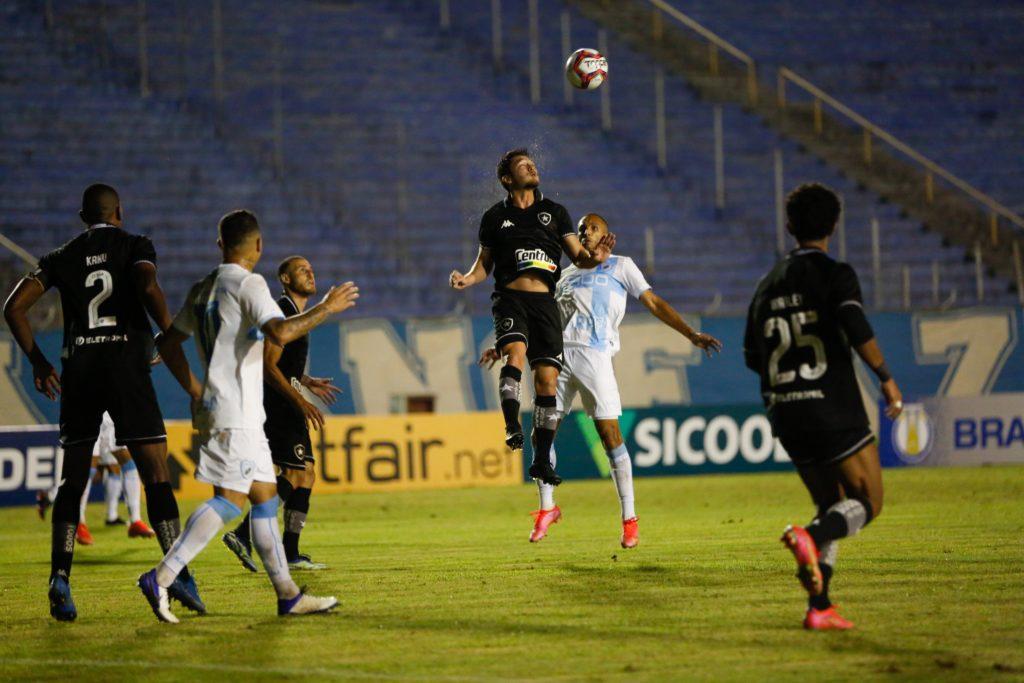 Volante do Botafogo Luis Oyama disputa uma bola de cabeça com adversário
