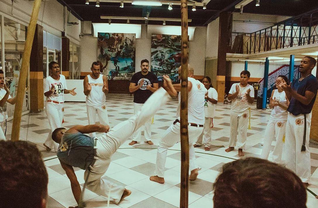 Na imagem, pessoas praticando capoeira