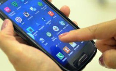 Imagem de uma mão segurando um celular