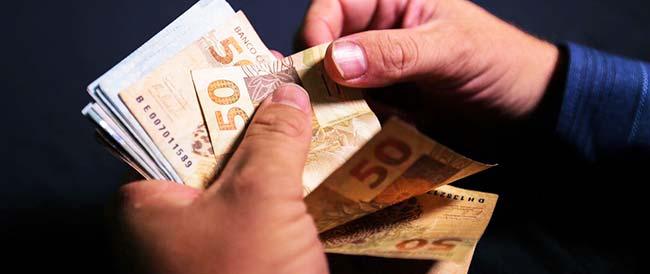 Pessoa contando notas de R$ 50