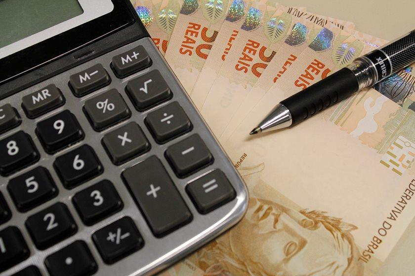Imagem de uma calculadora, dinheiro e caneta