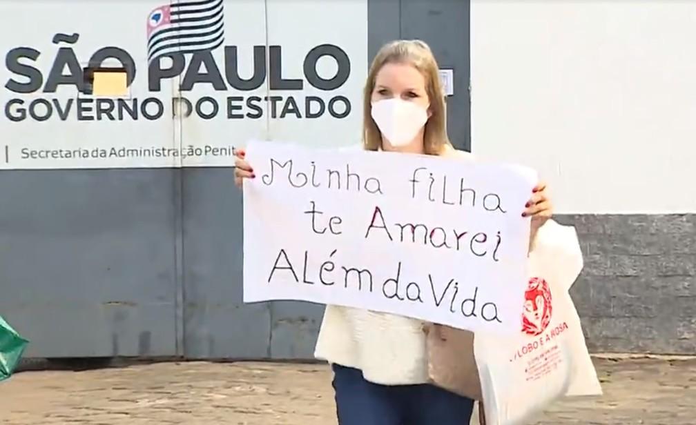 Elize Matsunaga exibe cartaz na saída de presídio