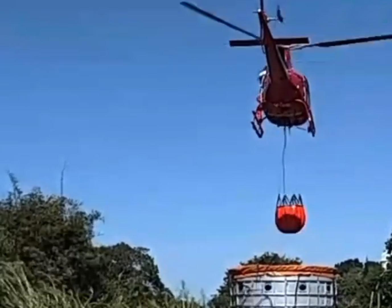 helicóptero do corpo de bombeiros capta água para jogar na mata