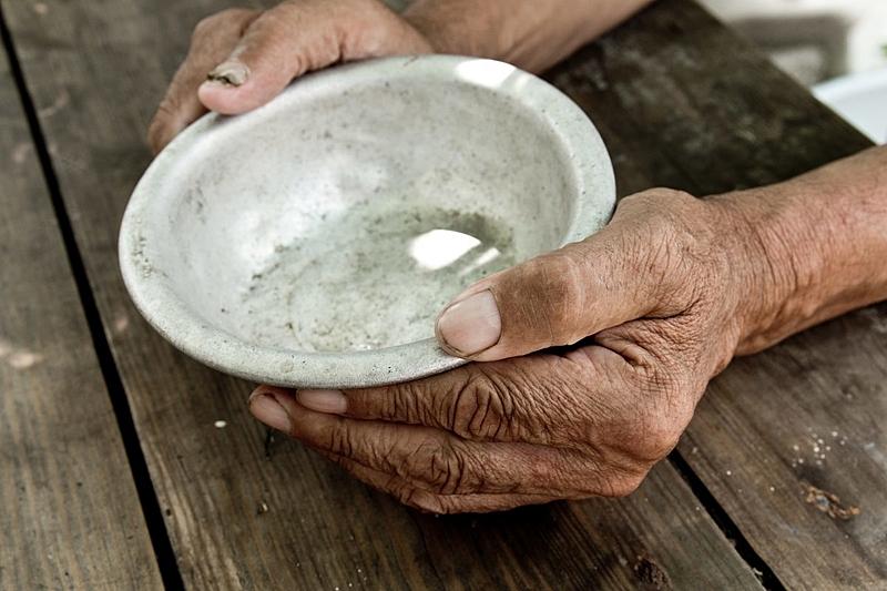 Senhora segurando prato de inox vazio