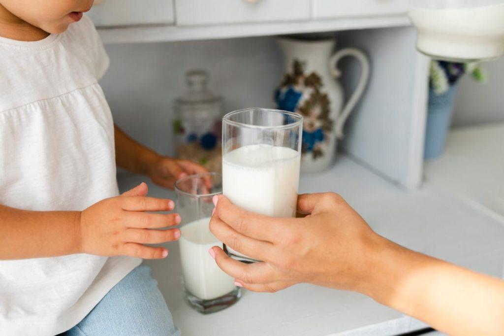 Imagem de uma criança recebendo um de leite